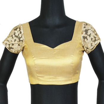Gold blouse with embroidered sleeves.